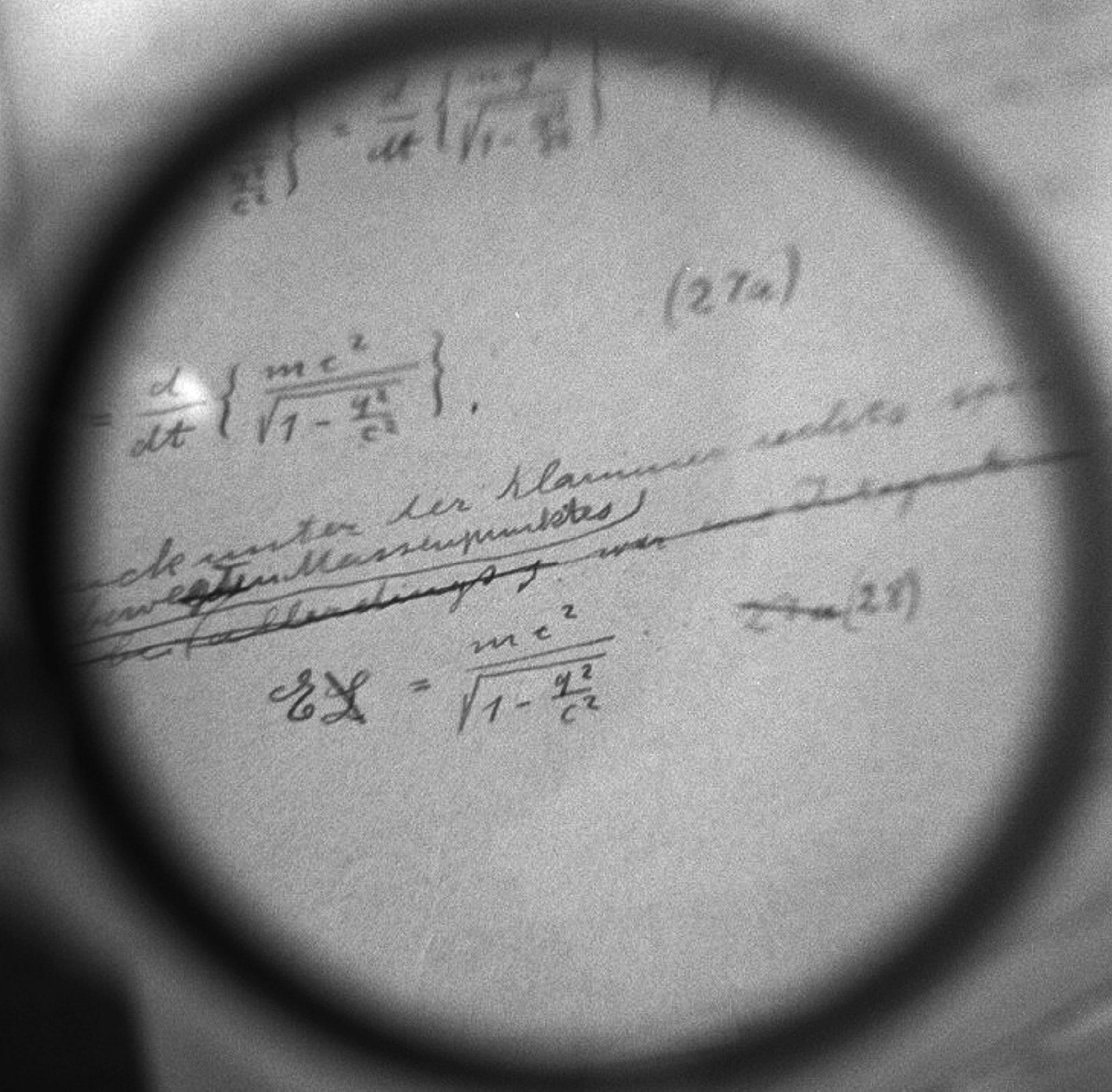Albert Einsteins Berechnungen zur Relativitätstheorie (E=mc2) sind unter einem Vergrößerungsglas auf dem Manuskript zu sehen.
