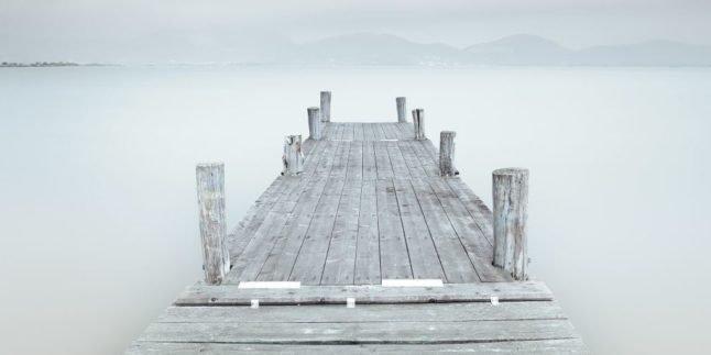 Grauer Steg über einem von Nebel bedeckten See