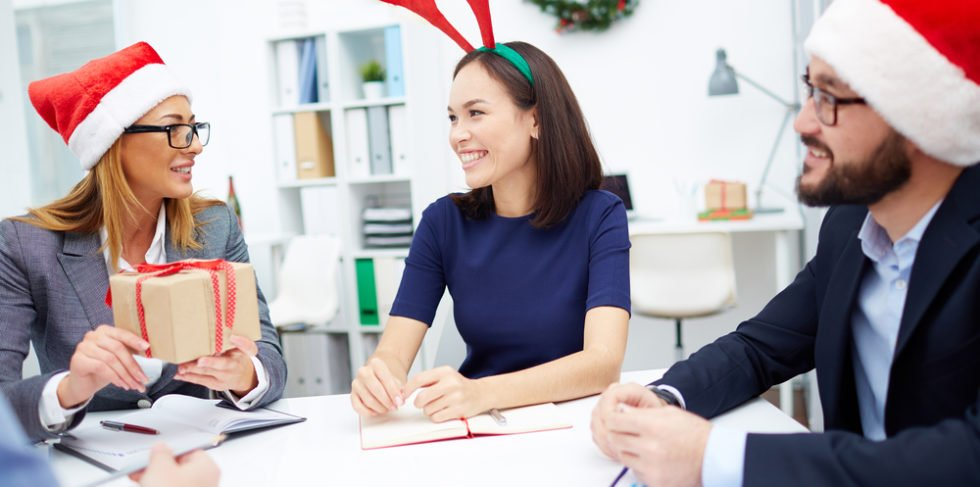 Zwei Frauen und ein Mann mit Weihnachtsmützen am Arbeitstisch