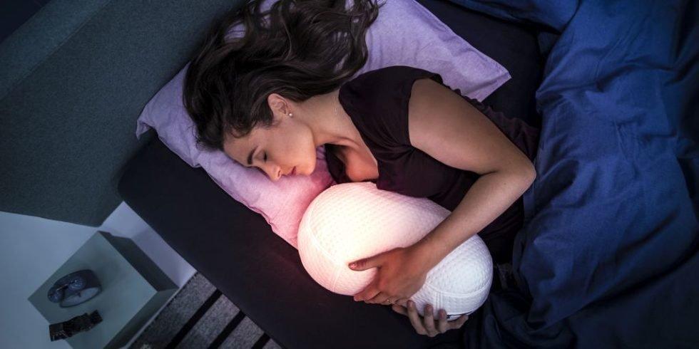 Frau mit Schlafroboter-Kissen im Arm