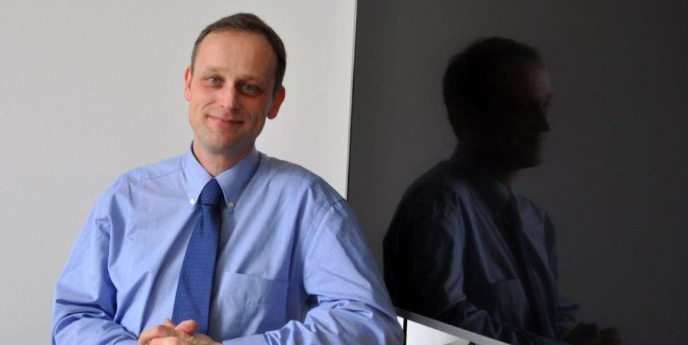 Prof. Egbert Figgemeier neben einem Flat-TV