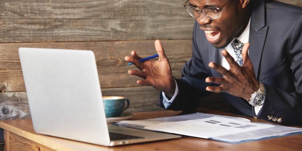 Mann im Anzug schaut auf Laptop und ärgert sich