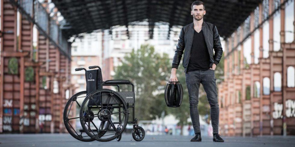 Rollstuhl mit Revolve Wheels und daneben Andrea Mocellin mit einem gefalteten Rad