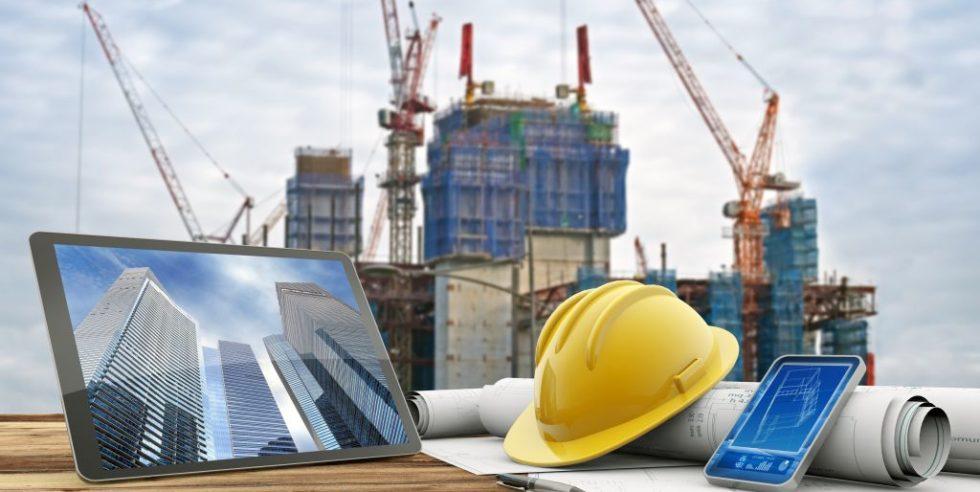Laptop, Tablet und Bauutensilien wie Bauhelm vor einer Baustelle