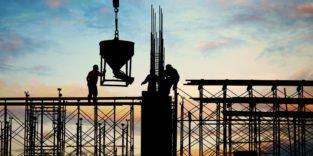 Bauarbeiter auf Stahlgerüst in der Dämmerung