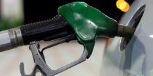 Grüne Zapfpistole tankt silbernes Auto