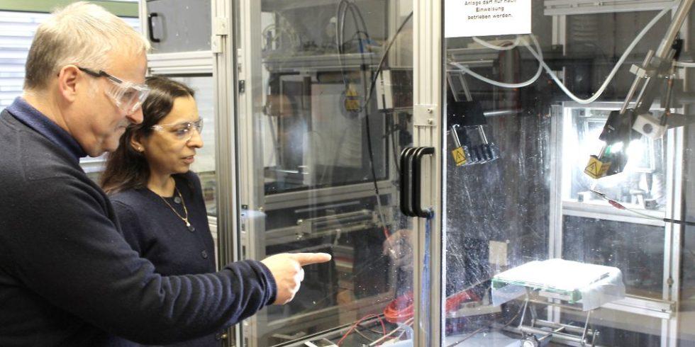 Andreas Greiner und Seema Agarwal an einer Anlage zum Elektrospinnen. Im Gegenlicht sind die dünnen Fasern zu erkennen, die den Vliesstoff bilden.