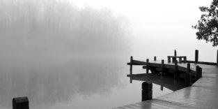 Schwarz-weiß Bild eines Stegs über nebligem Wasser