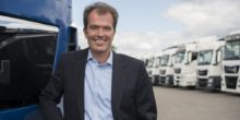 Rolf-Dieter Lafrenz steht vor einer Lkw-Flotte