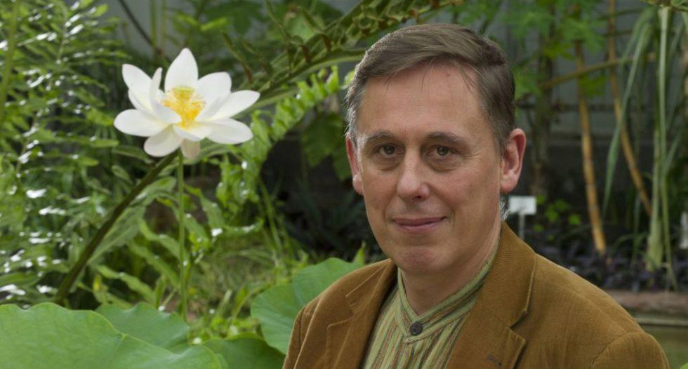 Prof. Dr. Peter Nick neben einer weiß-gelben Blüte.