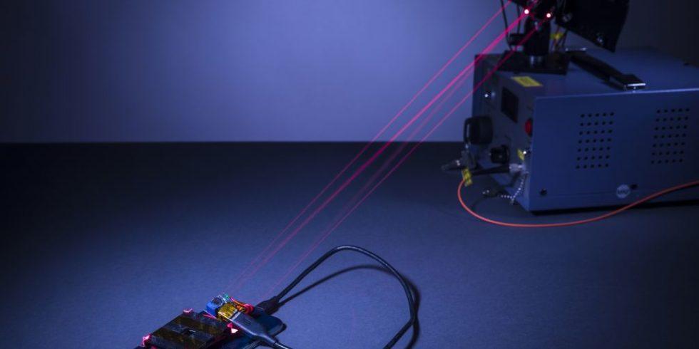 Dunkler Raum, in dem die Laserstrahlen vom Lasergerät zum Smartphone zus sehen sind