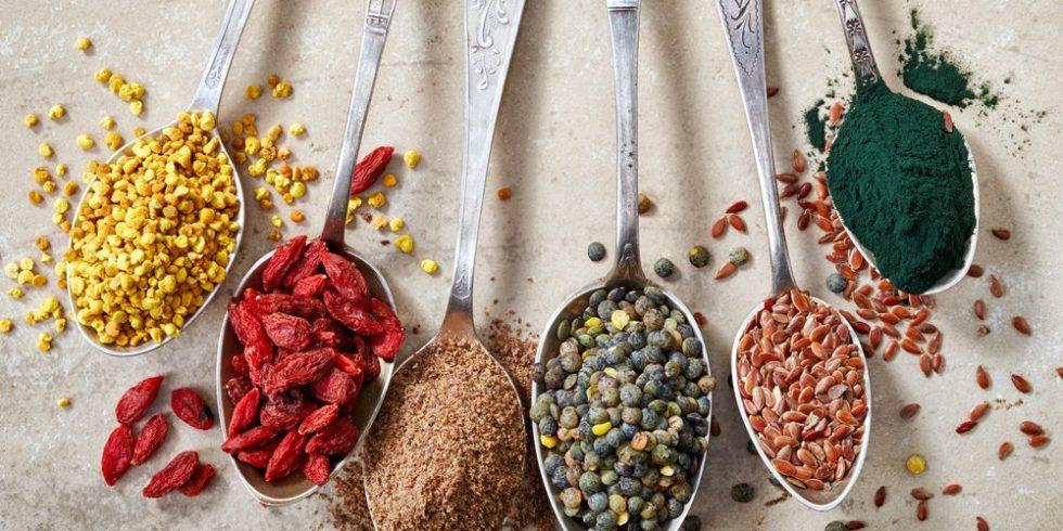 Sechs Löffel mit unterschiedlichen Gewürzen und Samen, z.B: Gojibeeren