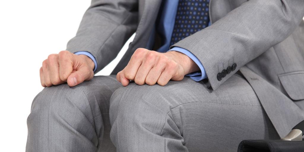 Mann im Anzug ballt die Hände auf den Knien zur Faust
