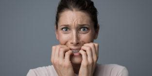 junge Frau, die verzweifelt auf ihren Fingernägeln kaut