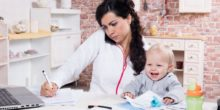 Frau mit kleinem Kind und Telefon am Ohr am Schreibtisch