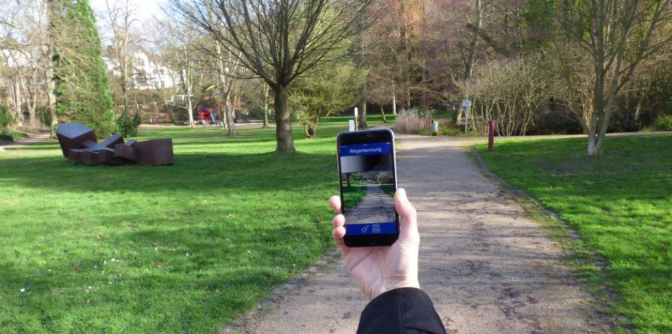 Zu sehen ist ein Park und eine Hand, die ein Smartphone mit geöffneter Camassia-App ins Bild hält.