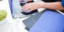 zwei Hände an einem Laptop, daneben liegen Bewerbungsmappen