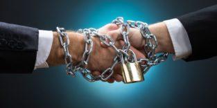 Zwei Hände beim Handschlag werden von einer dicken Eisenkette mit Schloss festgehalten