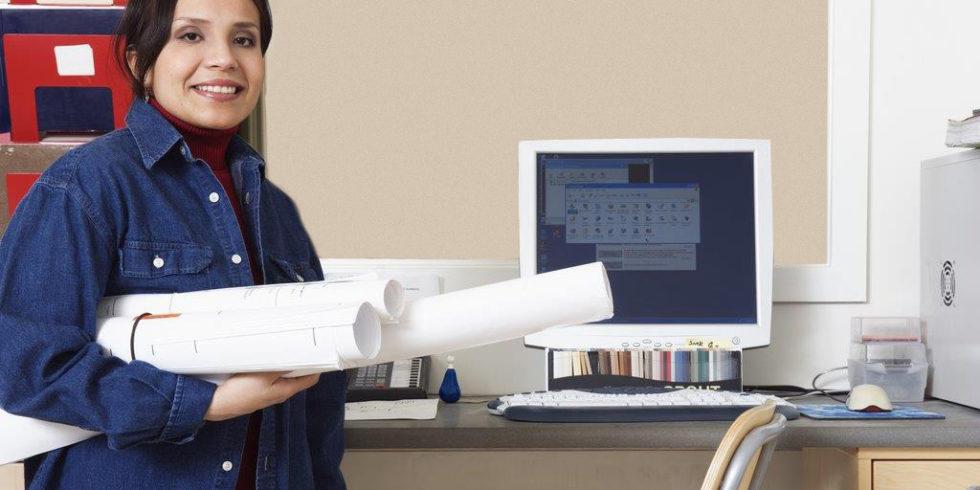 Frau mit Papierrollen im heimischen Büro