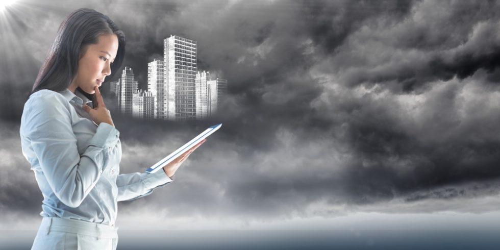 Frau mit Tablet und und Gebäudemodellen vor grauen Wolken
