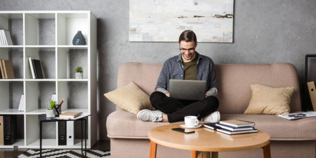 Mann mit Laptop auf dem Schoss auf dem Sofa