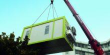 Ein Container, in dem sich die mobile Fabrik befindet, wird per Kran an seine Einsatzstelle befördert.