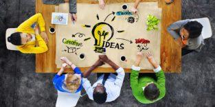 Kollegen sitzen um einen Tisch, auf dem eine Glühbirne das zentrale Element eines Mindmaps darstellt