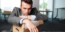 Mann im Anzug lehnt missmutig auf einer Kiste, in der Papier ist