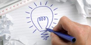Mann zeichnet Glühbirne auf einen Zettel