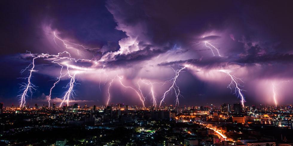 Gewitter über einer Großstadt bei Nacht