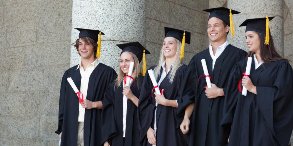 Fünf junge Menschen in schwarzer Absolventenkleidung