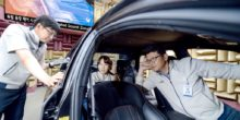Drei Kia-Mitarbeiter sitzen in einem Auto und lauschen