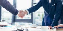 Zwei Männer im Anzug reichen sich die Hand über Besprechungstisch