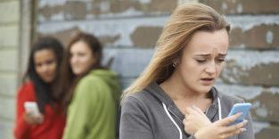 Mädchen tuscheln hinter dem Rücken eines Mädchens, das auf ihr Smartphone schaut
