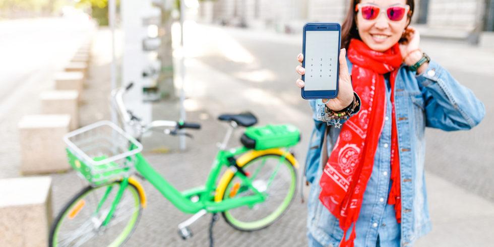 Grünes Leihrad steht hinter einer jungen Frau, die ihr Smartphone in die Kamera hält