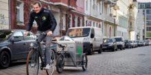 Fahrradkurier lädt Elektroautos auf