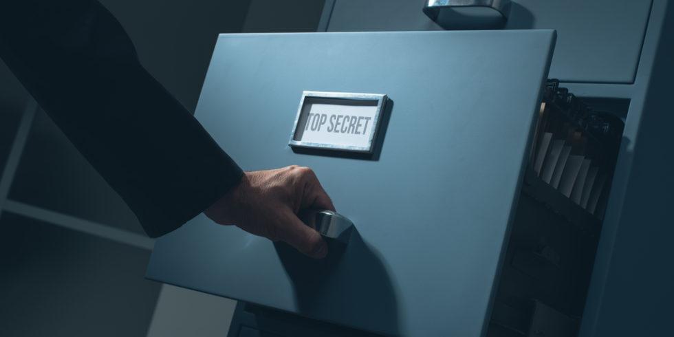 """Männerhand öffnet Schublade mit der Aufschrift """"Top Secret"""""""