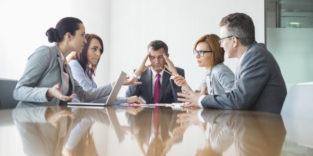 Fünf Kollegen sitzen am Besprechungstisch, vier scheinen sich zu streiten