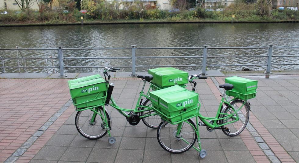 Grüne Lieferräder stehen an einem Fluss