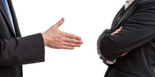 Zwei Menschen stehen sich gegenüber, einer streckt die Hand auf, der andere hält die Arme verschränkt