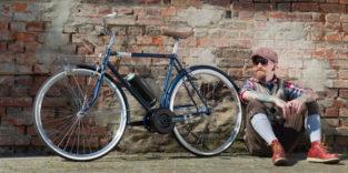Mann sitzt neben seinem Bike vor einer Backsteinwand