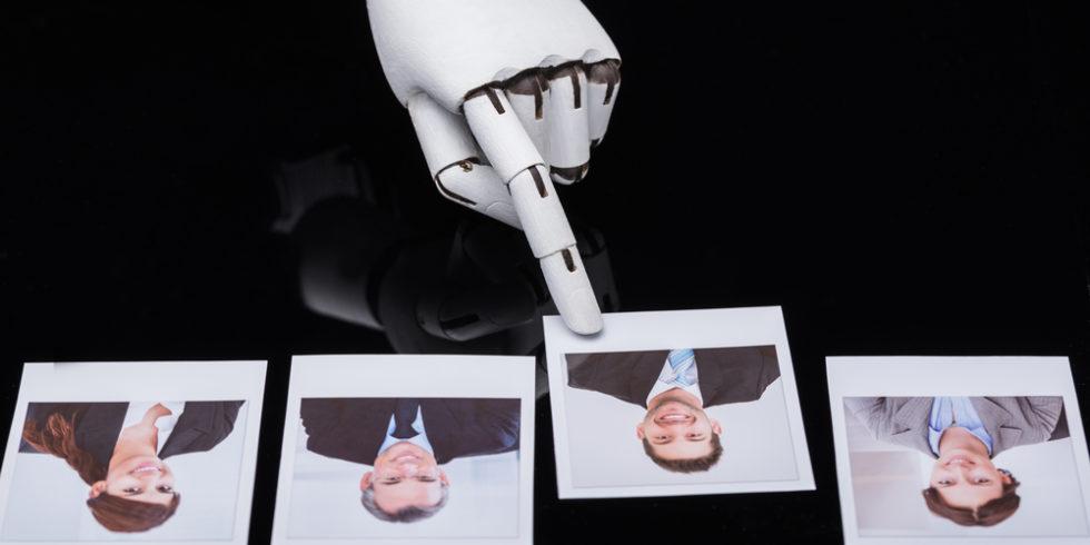 Roboterhand wählt ein Bewerbungsbild unter vieren aus