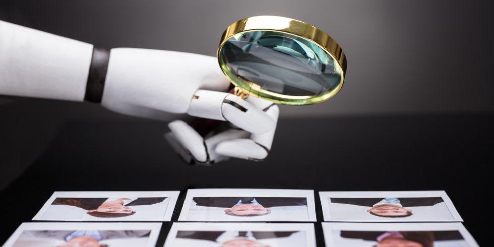 Roboterhand hält Lupe über Bewerbungsfotos