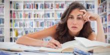 Junge Frau in einer Bibliothek hängt über einem Buch und schaut genervt in die Kamera