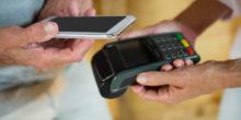 Männerhände halten NFC-Lesegerät und Smartphone