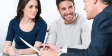 junges Paar sitzt vor einem Mann im Anzug, der Blatt und Stift hält