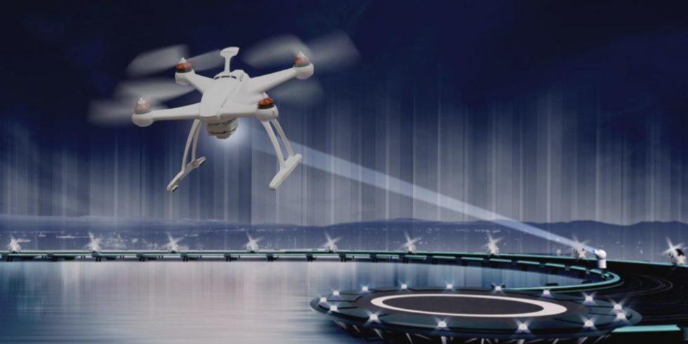 Drohne fliegt über einen See und wird von Laser vom Boden angestrahlt