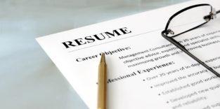 Blatt Papier mit der Aufschrift Resume, darauf ei Stift und eine Brille