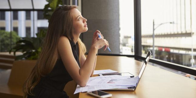 Junge Frau mit Unterlagen und Laptop schaut aus dem Fenster
