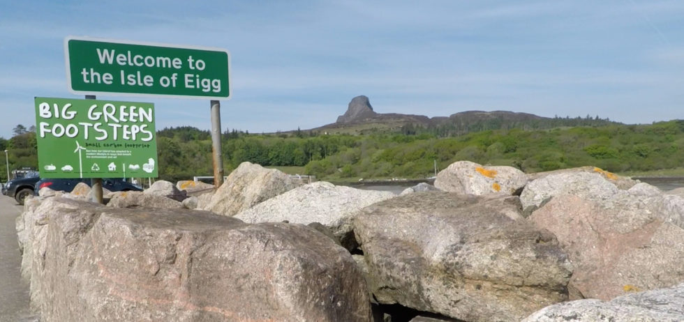 """Schild """"Welcome to Isle of Eigg"""" vor grüner Hügellandschaft"""